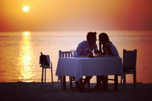 A young couple gazing into each other's eyes while having dinner on the beach